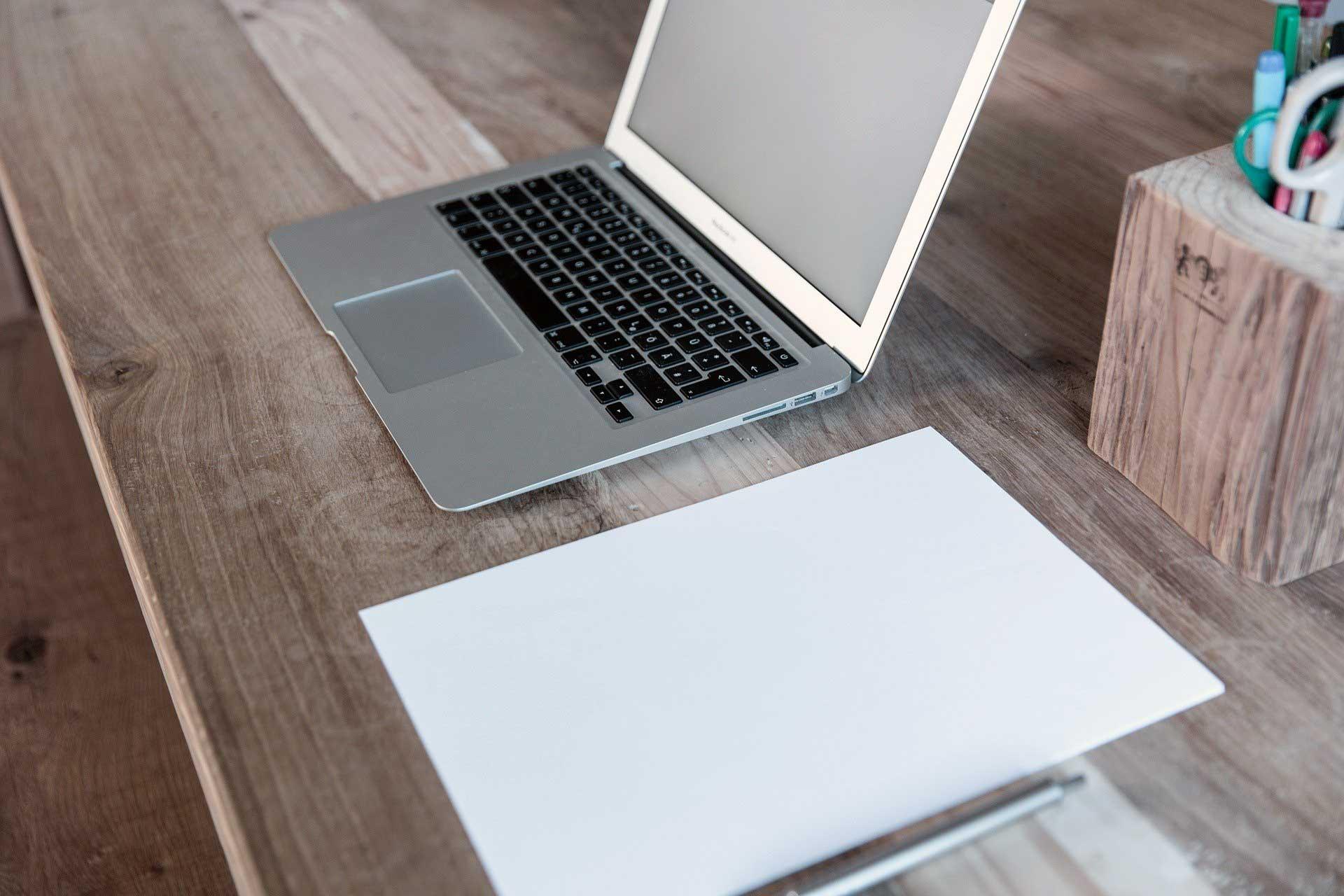 Masa uzerinde laptop ve kagit-kalem