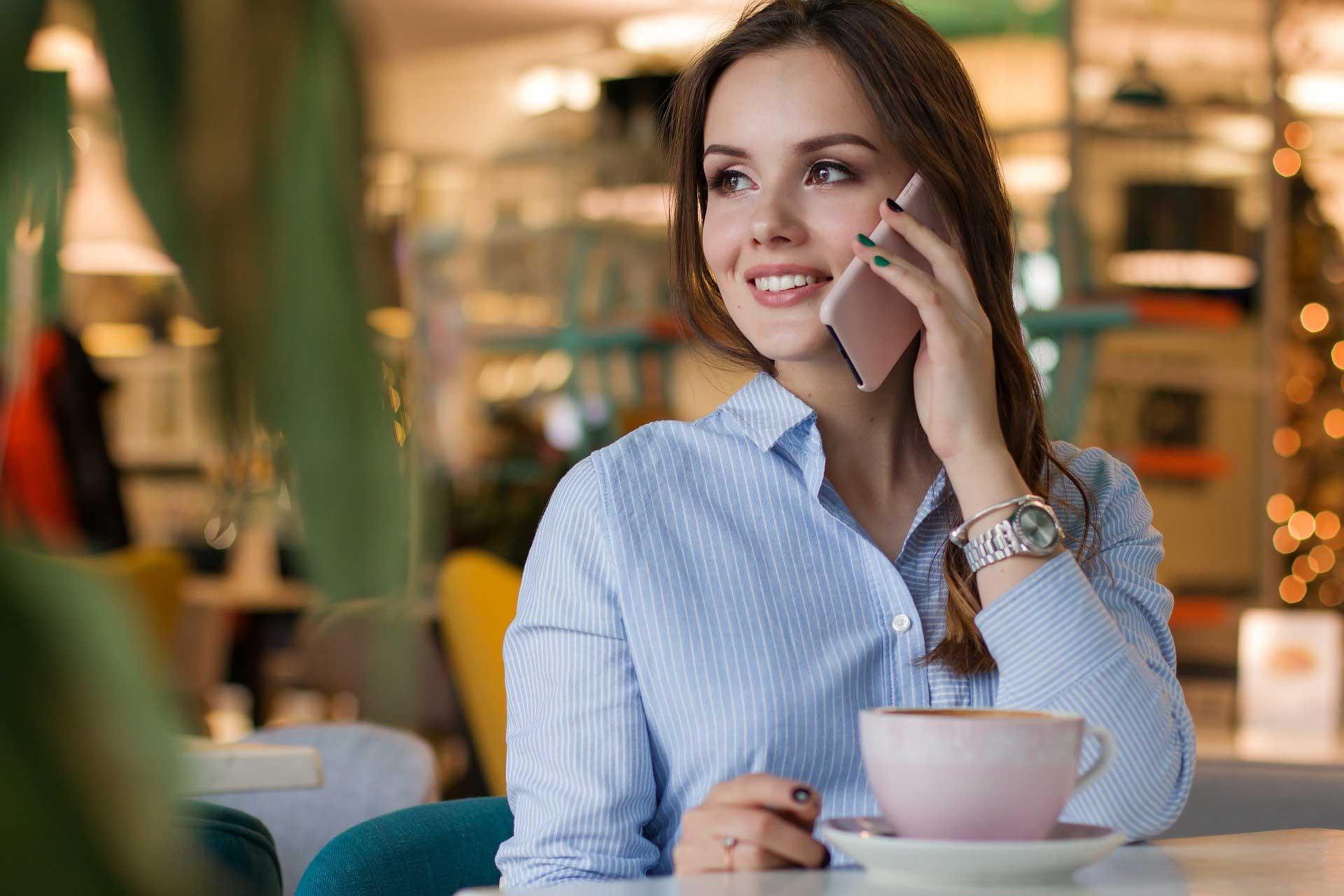 Kahve icerken telefon kullanan kadin.